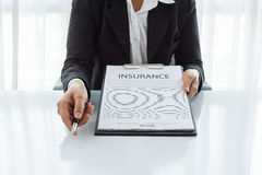 Young woman in suit in his office showing an insurance policy an. D pointing with a pen where the policyholder must to sign Royalty Free Stock Photography