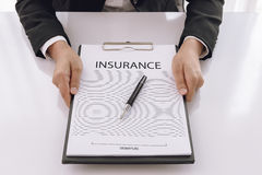Young woman in suit in his office showing an insurance policy an Stock Photos