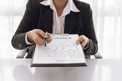 Young woman in suit in his office showing an insurance policy an Stock Image