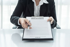 Young woman in suit in his office showing an insurance policy an. D pointing with a pen where the policyholder must to sign Royalty Free Stock Images