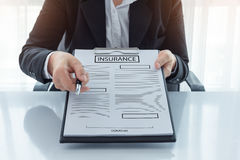 Young woman in suit in his office showing an insurance policy an Royalty Free Stock Image