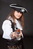 Young woman in suit of the pirate aims a pistol Stock Photos