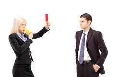 Young woman in a suit showing a red card and blowing a whistle t Stock Image