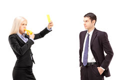 Young woman in a suit showing a yellow card to a young businessm Stock Photography