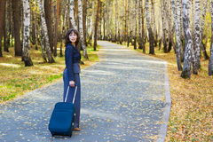 Young fashion business woman with a suitcase walking on the road Stock Photos
