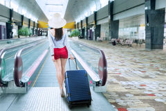 Young woman with a suitcase on the airport. Young woman with a suitcase walking to escalator at airport Royalty Free Stock Photo
