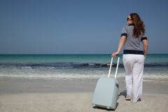 Young woman with suitcase on the beach Royalty Free Stock Images