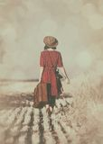 Young woman with suitcase and camera. Photo of the beautiful young woman with camera and brown suitcase walking in the field Stock Photo