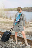 Young woman with a suitcase and a camera on the rails Stock Photography