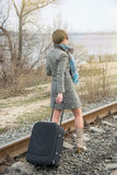 Young woman with a suitcase and a camera on the rails Royalty Free Stock Photography