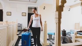 Young woman with suitcase check-in to the hotel. stock images