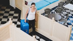 Young woman with suitcase check-in to the hotel. royalty free stock photo