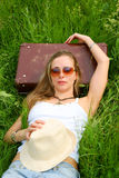Young woman with suitcase on grass Stock Photo
