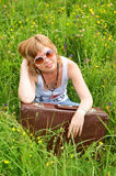 Young woman with suitcase on grass Royalty Free Stock Image