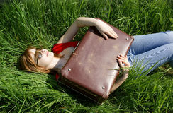 Young woman with suitcase on grass Stock Images