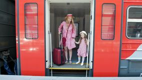 Young woman with suitcase and her little daughter leaves the train car stock video