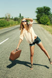 Young woman with suitcase hitchhiking along a road. Attractive young woman with suitcase hitchhiking along a road Royalty Free Stock Photography