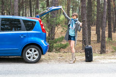 Young woman with a suitcase is hitchhiking on a forest road. Pointing her thumb up Royalty Free Stock Photo