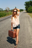 Young woman with suitcase hitchhiking on road in countryside Royalty Free Stock Photos