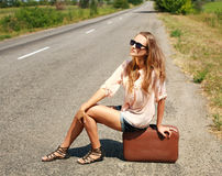 Young woman with suitcase hitchhiking on road in countryside Stock Images