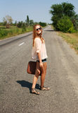 Young woman with suitcase hitchhiking on road in countryside. Young woman in the summer with a suitcase hitchhiking on the road in the countryside Royalty Free Stock Photo