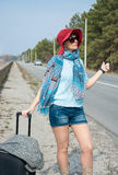 Young woman with a suitcase is hitchhiking on road near the sea. Pointing her thumb up Stock Photos