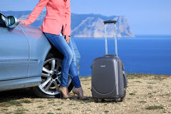 Young woman with suitcase leaning against on car hood. On background sea and mountains. Business trip to travel Stock Photos