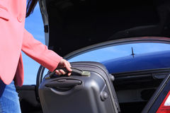 Young woman with a suitcase near the car trunk Royalty Free Stock Photos