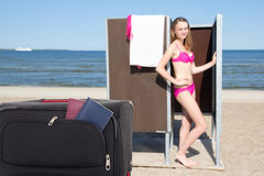 Young woman and suitcase with passports on the beach Stock Image