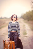 Young woman with suitcase. Photo of the beautiful young woman with suitcase on the countryside road Royalty Free Stock Photo