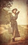 Young woman with suitcase. Photo of the beautiful young woman with suitcase on the countryside road Stock Photography