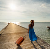 Young woman with suitcase on the pier Stock Images
