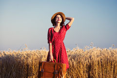 Young woman with suitcase. Portrait of the beautiful young woman with brown suitcase walking in the field Stock Images