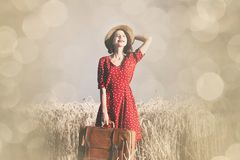 Young woman with suitcase. Portrait of the beautiful young woman with brown suitcase walking in the field Royalty Free Stock Photo