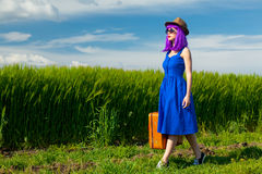 Young woman with suitcase. Portrait of young beautiful woman with suitcase in the field Royalty Free Stock Images