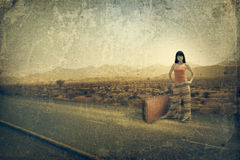 Young woman with suitcase on the road Stock Photography