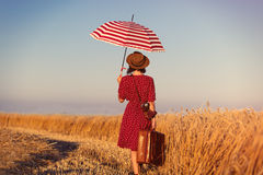 Young woman with suitcase, umbrella and camera Stock Photos