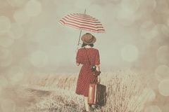 Young woman with suitcase, umbrella and camera. Photo of the beautiful young woman with camera, umbrella and brown suitcase walking in the field Stock Photo