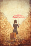 Young woman with suitcase and umbrella Stock Images