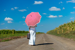 Young woman with suitcase and umbrella Stock Image