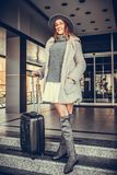 Young woman with a suitcase waiting for taxi front of hotel doo. Beautiful and attractive young woman with a suitcase waiting for taxi front of hotel door Royalty Free Stock Photos