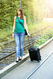 Young woman with suitcase walking along a track Stock Image