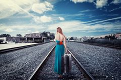 Young woman with suitcase walking away on rail tracks talking on phone Royalty Free Stock Photos