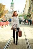 Young woman with a suitcase walking through the street Royalty Free Stock Photography