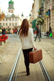 Young woman with a suitcase walking through the street Royalty Free Stock Images
