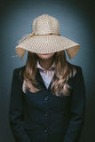 Young woman in suite and straw hat standing on gray background Royalty Free Stock Photo