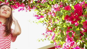 Young woman in the summer on a background of beautiful exotic flowers stock footage