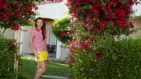 Young woman in the summer on a background of beautiful exotic flowers stock video