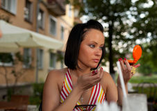Young woman in summer cafe applying cosmetics Royalty Free Stock Image