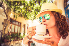 Young woman in summer cafe. Young beautiful woman drinking coffee in summer cafe outdoors Royalty Free Stock Photos